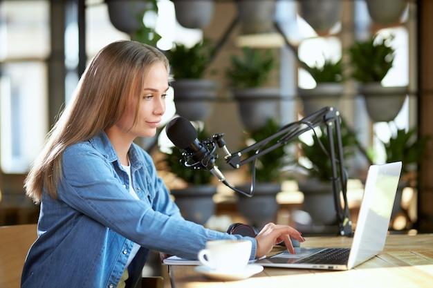 Junge frau, die im laptop mit modernem mikrofon arbeitet