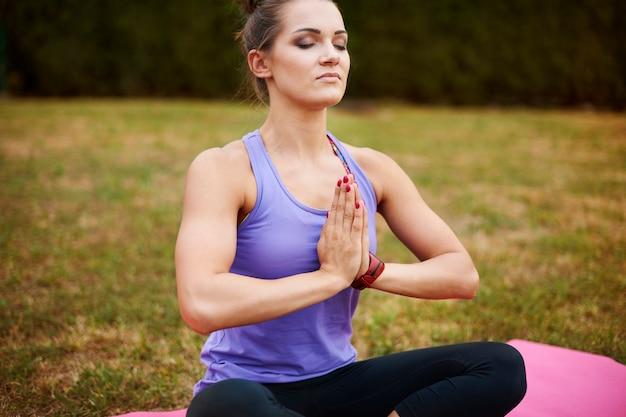 Junge frau, die im park meditiert. zen-ähnliche position in einem meiner favoriten