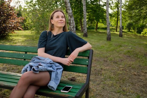 Junge frau, die im park sitzt, der auf einem stuhl sitzt