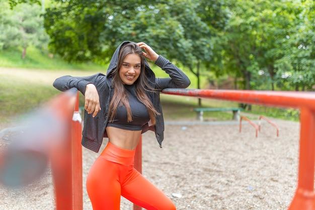 Junge frau, die im park trainiert. kaukasisches weibliches eignungsmodell, das morgens ausarbeitet