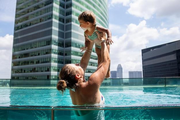 Junge frau, die im pool mit kleinem kleinkindmädchen spielt
