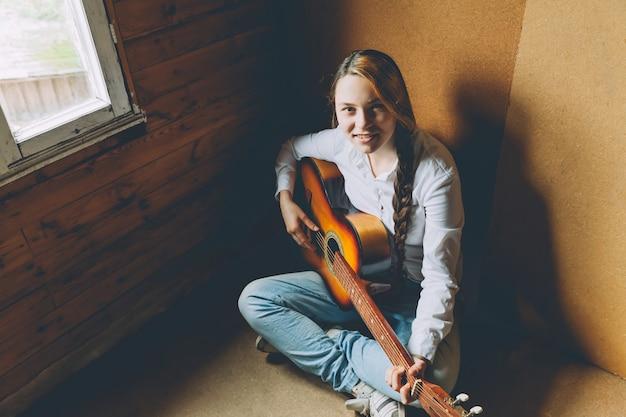 Junge frau, die im raum auf boden sitzt und zu hause gitarre spielt