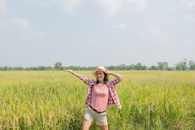 Junge frau, die im reisfeld in thailand geht. reisen sie zu sauberen orten der erde und entdecken sie die schönheit der natur. junge frau reisender mit hut stehend.