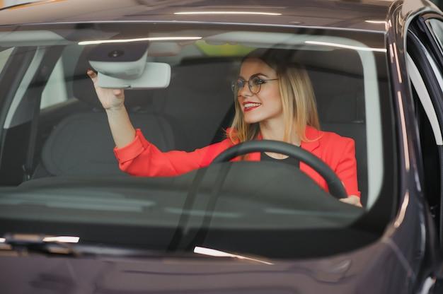 Junge frau, die im rückspiegel eines autos schaut