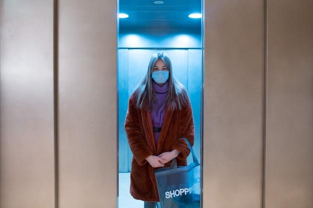 Junge frau, die im schließenden aufzug in medizinischer gesichtsmaske coronavirus covid-pandemie und einkaufskonzept steht