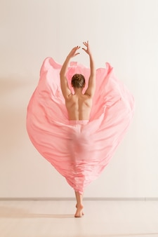 Junge frau, die im schönen rosa kleid tanzt