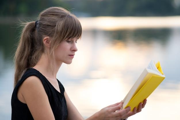 Junge frau, die im sommerpark stillsteht und ein buch liest. bildungs- und studienkonzept.