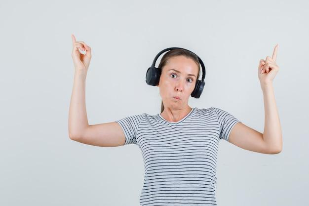 Junge frau, die im t-shirt, in den kopfhörern zeigt und verwirrt schaut. vorderansicht.