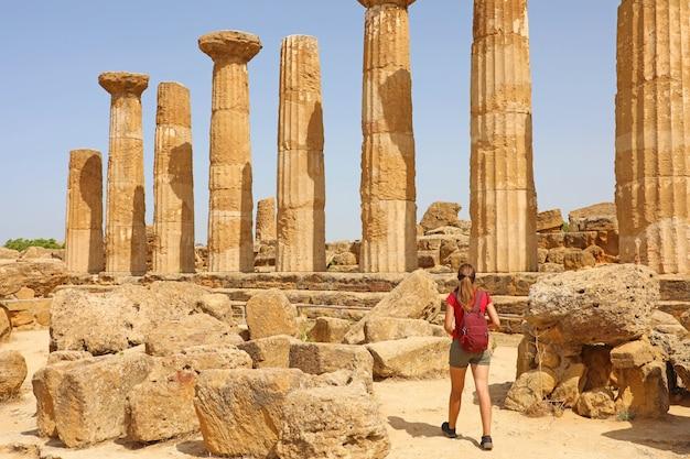 Junge frau, die im tal der tempel agrigento, sizilien geht. reisende mädchen besucht griechische tempel in süditalien.