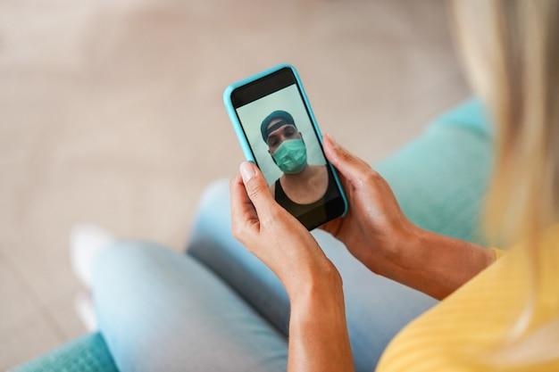 Junge frau, die im videoanruf mit freund unter verwendung des mobiltelefons plaudert, während er im freien geht und sicherheitsmaske trägt