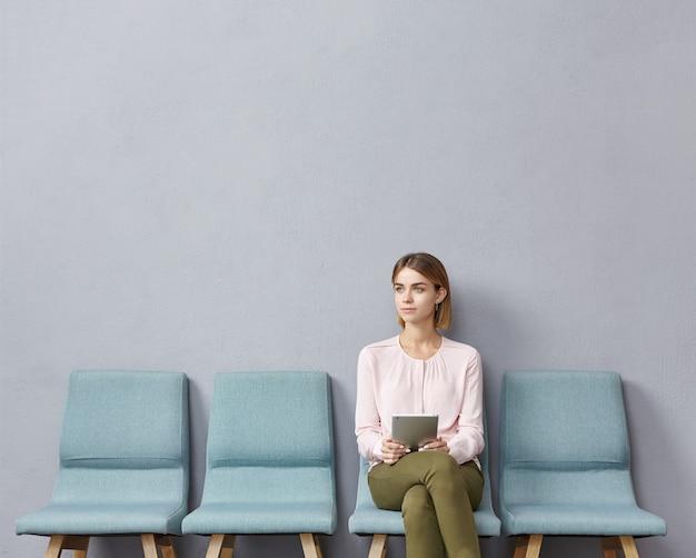 Junge frau, die im wartezimmer sitzt