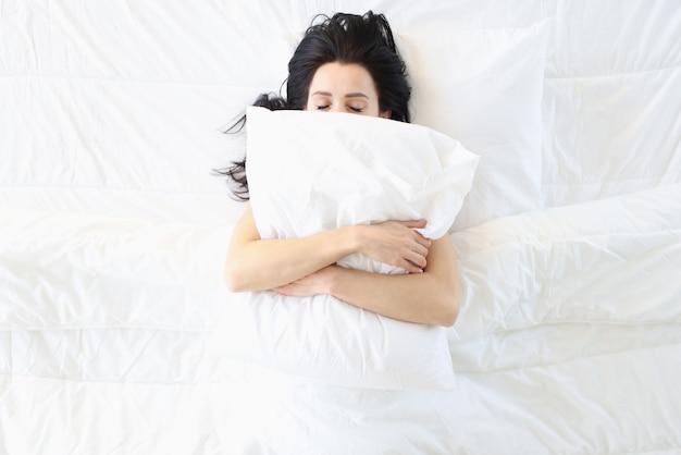 Junge frau, die im weißen bett mit kissen auf ihrer gesichtsoberansicht schläft. komfortables und weiches bettkonzept