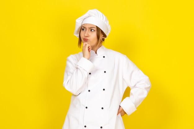 Junge frau, die im weißen kochanzug und im weißen kappen denkenden ausdruck kocht