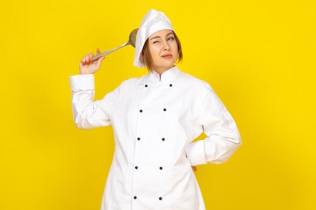 Junge frau, die im weißen kochanzug und in der weißen kappe kocht, die denkend hält, silbernen löffel haltend