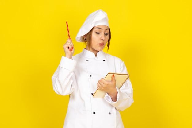 Junge frau, die im weißen kochanzug und in der weißen kappe kocht, die notizen aufschreiben