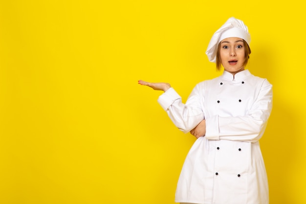 Junge frau, die im weißen kochanzug und in der weißen kappe kocht, überrascht überrascht