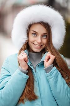 Junge frau, die im winterpark geht. winterpark im schnee. kleidungswerbefotokonzept.