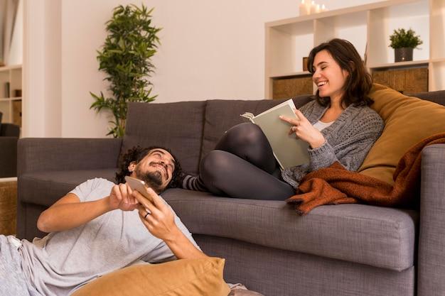 Junge frau, die im wohnzimmer neben ihrem ehemann liest