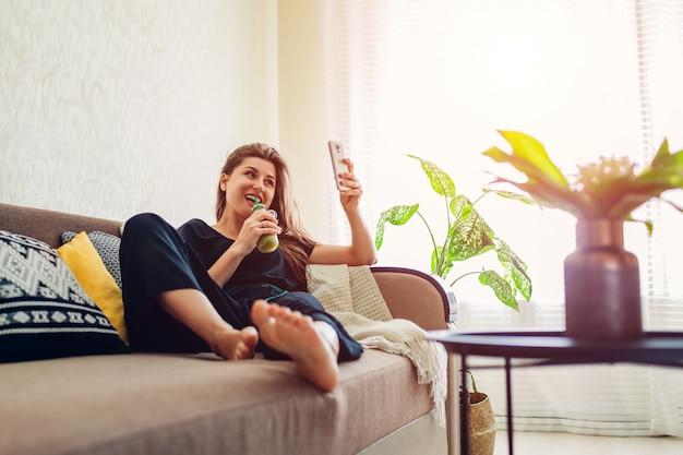 Junge frau, die im wohnzimmer sich entspannt und smoothie unter verwendung des smartphone trinkt. gesunde ernährung