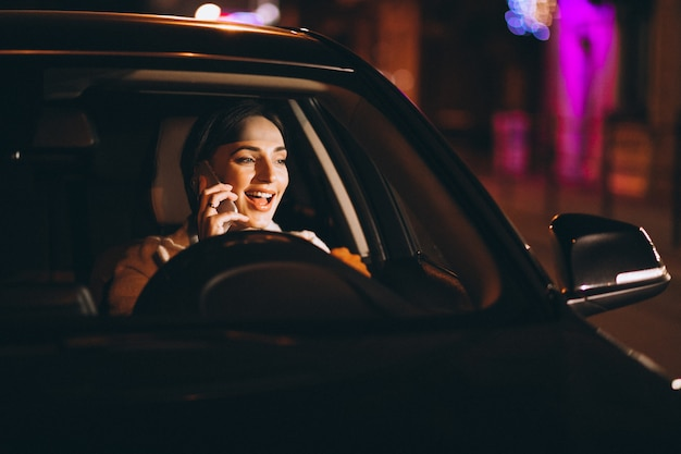 Junge frau, die in auto nachts fährt