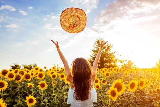 Junge frau, die in blühenden werfenden hut des sonnenblumenfeldes geht und spaß hat. sommerurlaub