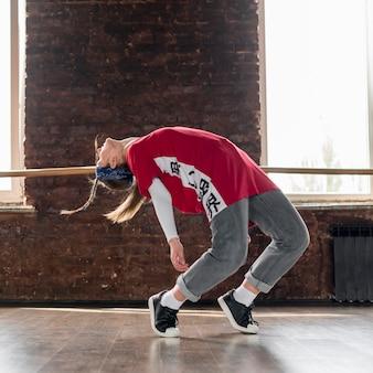 Junge frau, die in das tanzstudio breakdancing ist