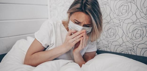 Junge frau, die in den armen hustet krank von der coronavirus-virusinfektion, die das corona-virus verbreitet, das mund und nase bedeckt. schmerzhafter husten kranker patient, der im bett zu hause quarantäneisolation liegt. erste symptome