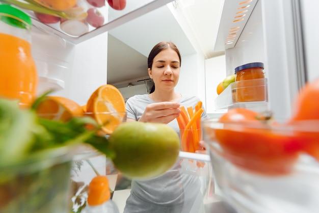 Junge frau, die in den kühlschrank schaut