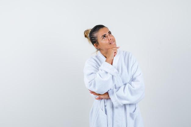 Junge frau, die in denkender pose im bademantel steht und nachdenklich aussieht