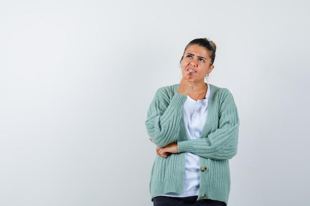 Junge frau, die in denkender pose in weißem hemd und mintgrüner strickjacke steht und nachdenklich aussieht