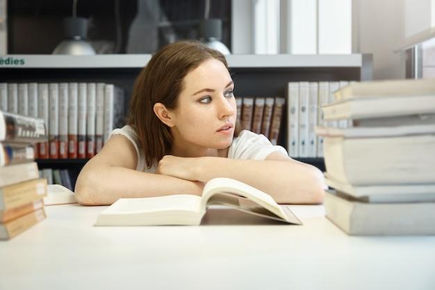 Junge frau, die in der bibliothek sitzt