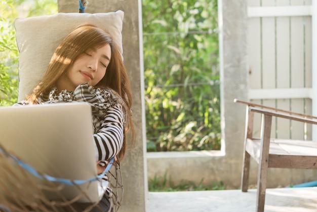 Junge frau, die in der hängematte schläft, während laptop verwendet wird, freiberuflicher lebensstil konzeptionell, arbeit überall
