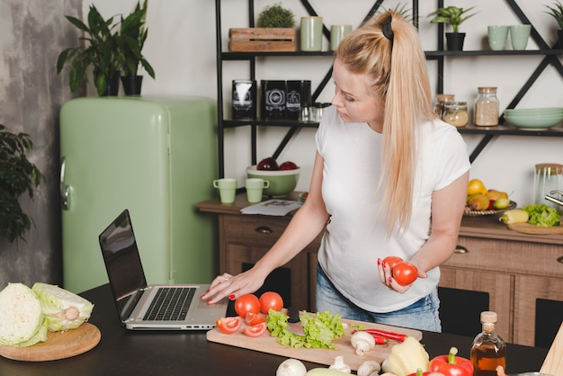 Junge frau, die in der hand rote tomaten unter verwendung des laptops in der küche hält