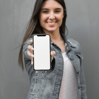 Junge frau, die in der hand smartphone zeigt