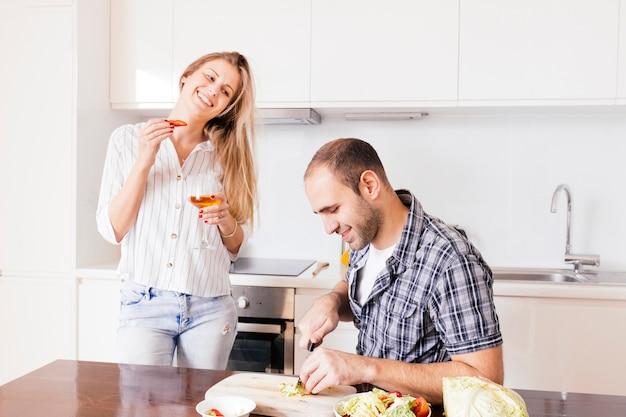 Junge frau, die in der hand weinglas betrachtet ihren ehemann betrachtet das gemüse in der küche hält