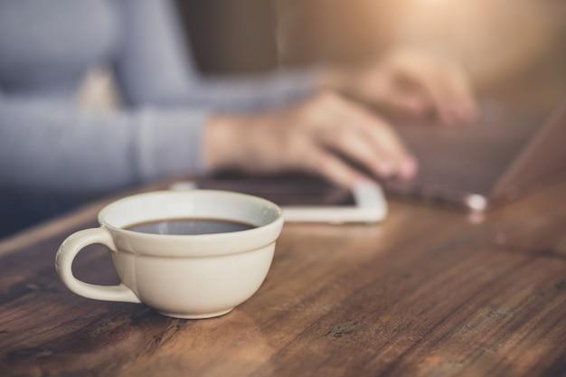 Junge frau, die in der kaffeestube am holztisch sitzt, kaffee trinkt und laptop verwendet.