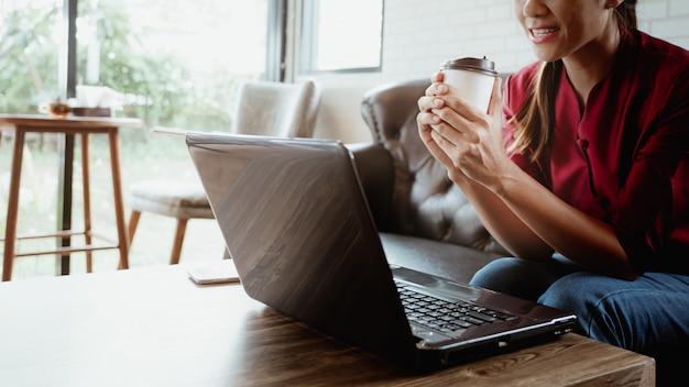 Junge frau, die in der kaffeestube mit dem halten der heißen kaffeepapierschale sitzt.