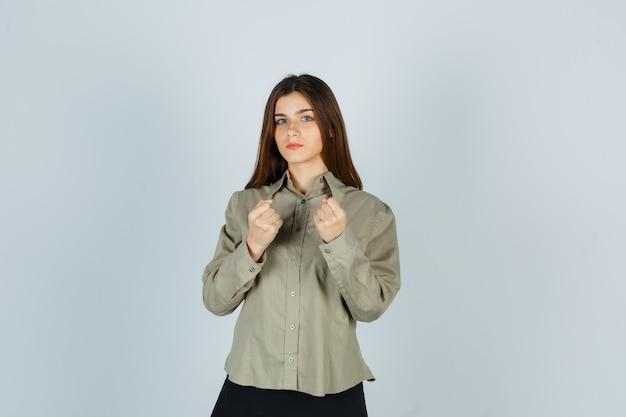 Junge frau, die in der kampfpose in hemd, rock steht und selbstbewusst aussieht. vorderansicht.