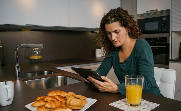 Junge frau, die in der küche frühstückt und auf das tablet schaut