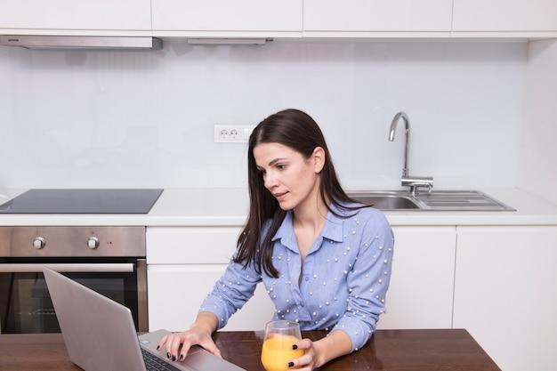 Junge frau, die in der küche hält glas saft unter verwendung des laptops sitzt