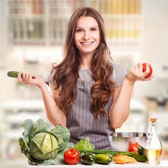 Junge frau, die in der küche kocht. gesundes essen - gemüsesalat. diät. diät konzept. gesunder lebensstil.