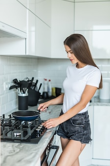 Junge frau, die in der küche kocht
