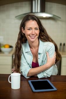 Junge frau, die in der küche mit kaffeetasse und digitaler tablette auf worktop lächelt
