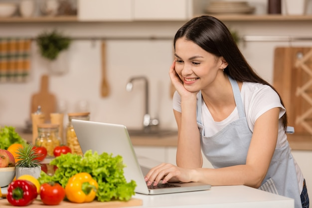 Junge frau, die in der küche mit tablet-computer steht und rezepte schaut, lächelnd. food blogger konzept