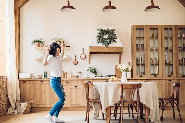 Junge frau, die in der küche tanzt