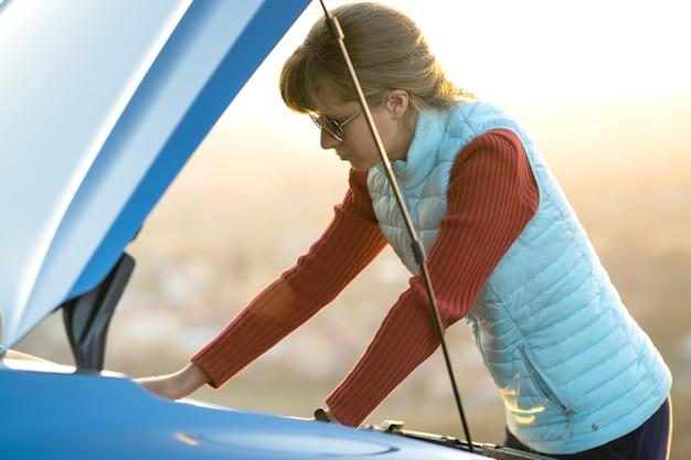 Junge frau, die in der nähe eines kaputten autos mit aufgeklappter motorhaube steht und probleme mit ihrem fahrzeug hat.