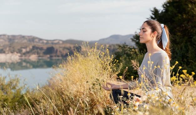 Junge frau, die in der natur meditiert