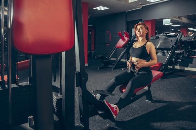 Junge frau, die in der turnhalle mit ausrüstung übt. athletisches weibliches model macht übungen