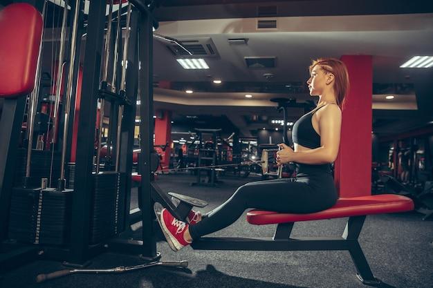 Junge frau, die in der turnhalle mit ausrüstung übt. athletisches weibliches modell, das übungen macht, körper trainierend