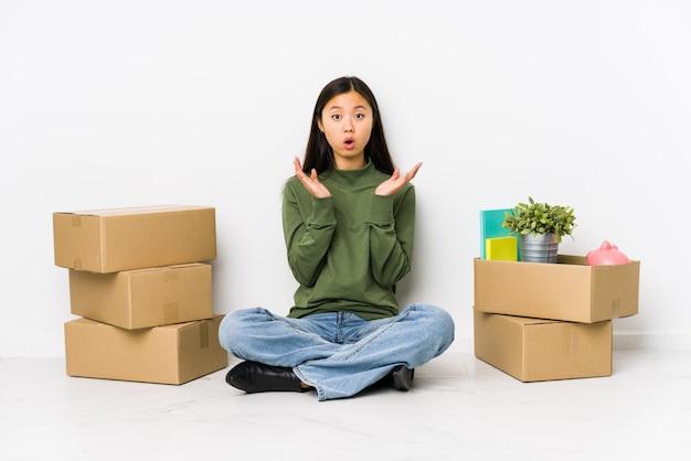 Junge frau, die in ein neues zuhause zieht, überrascht und schockiert